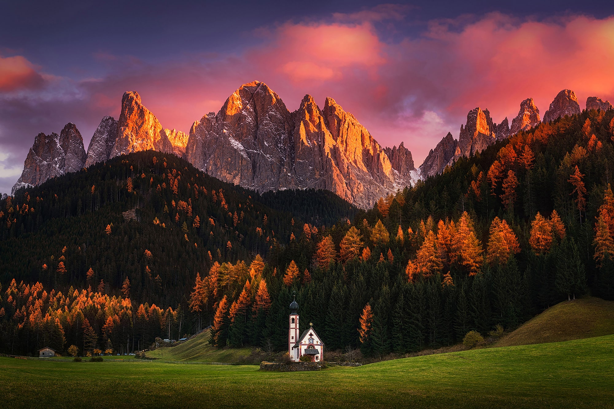 albert dros sony alpha 7RII a small church sits in the shadow of a mountain with the peaks illuminated in golden orange