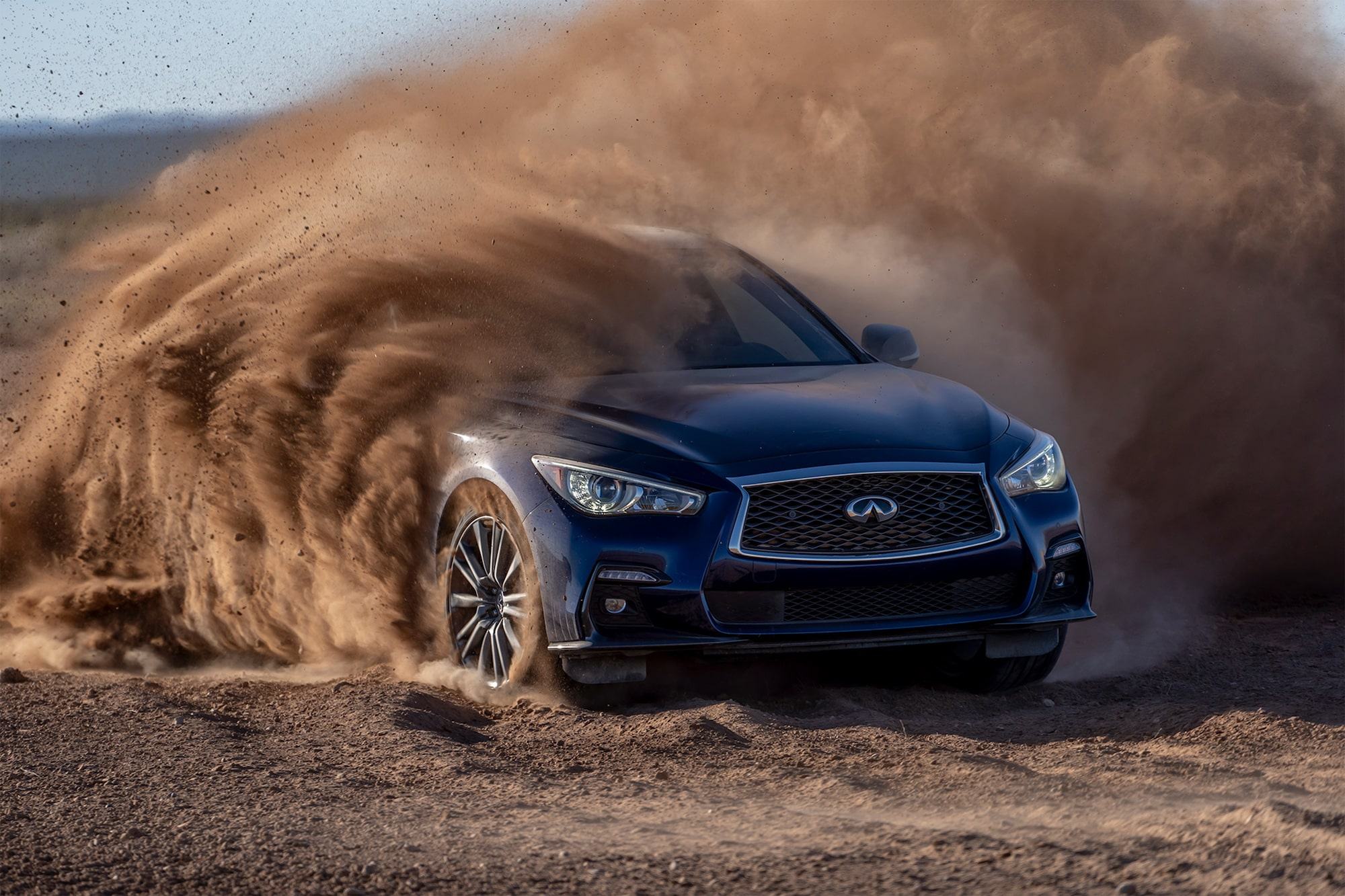 dominic fraser sony alpha 7III car turns quickly in the desert and throws up a cloud of dust