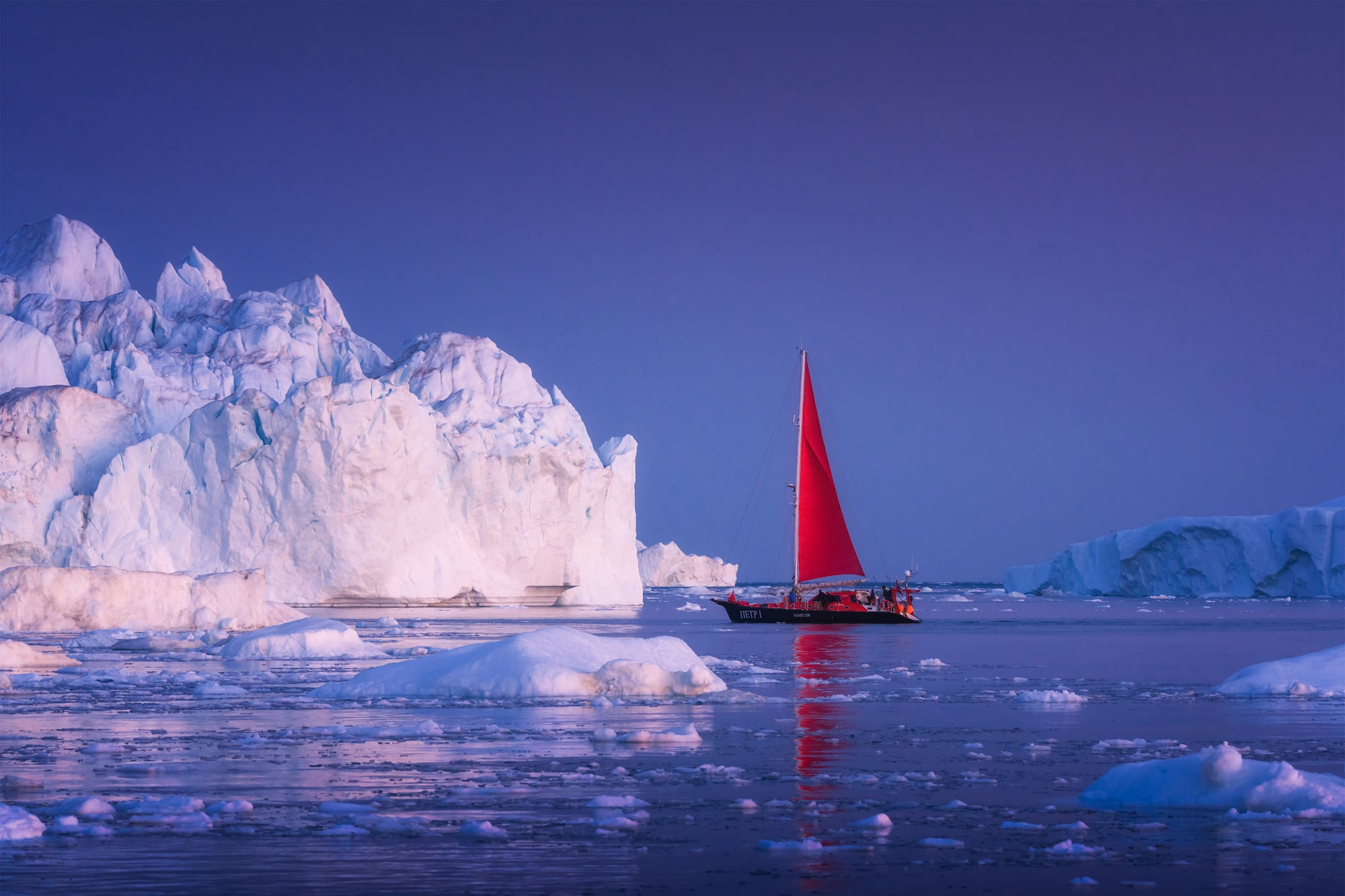 albert dros sony alpha A7RM4 a red sailed ship cruises gently in front of a sunlit iceberg