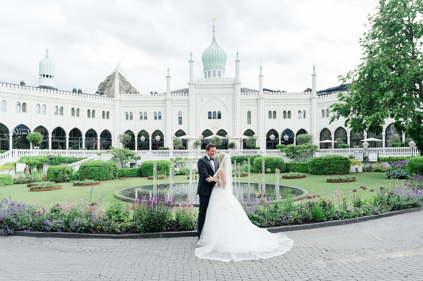 sandra aberg sony alpha 7r3 the bride and the groom hold one another in front of a luxurious garden and building