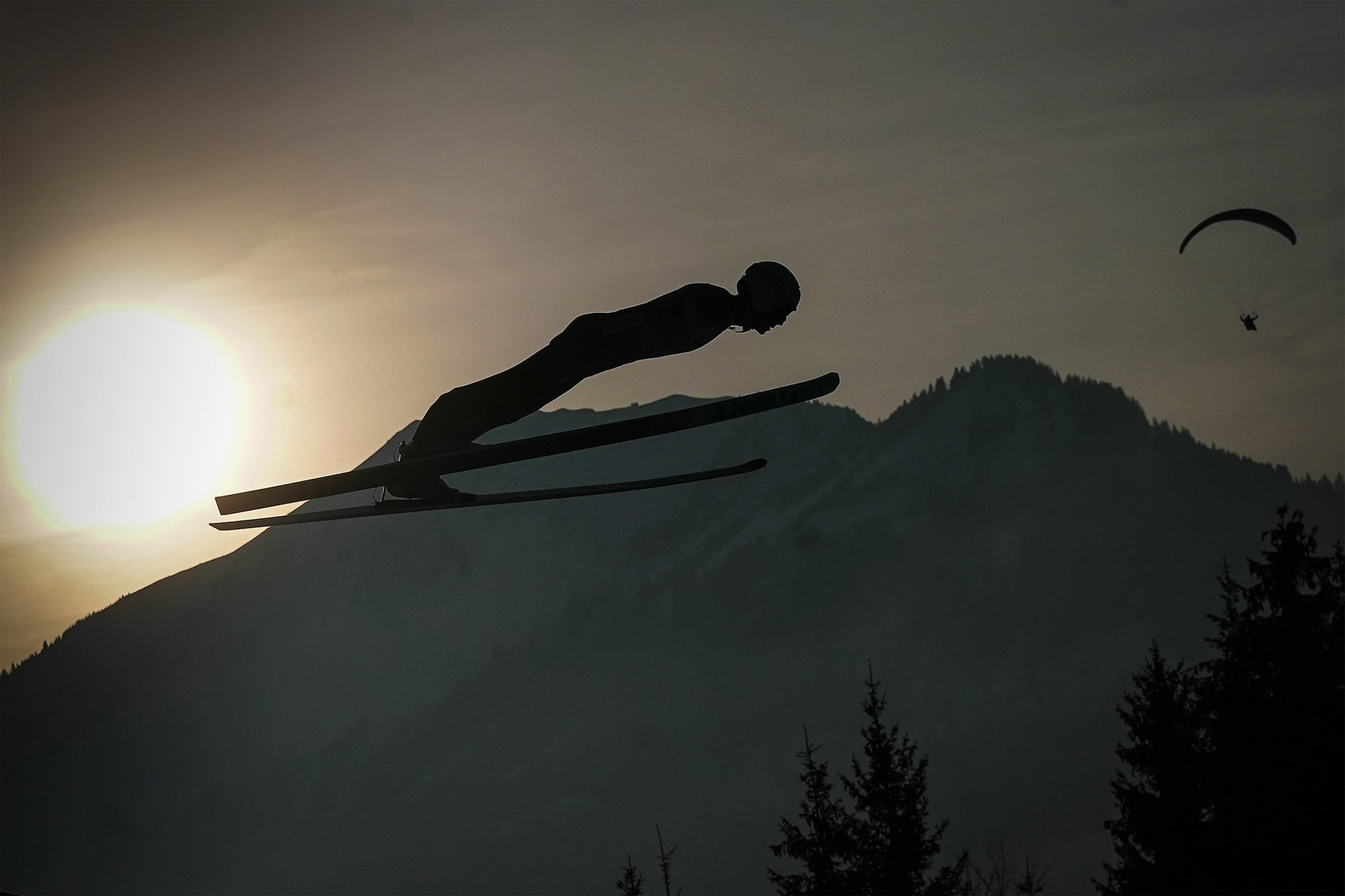 tomasz markowski sony alpha 9 ski jumper sideways silhouetted against the sun with a paraglider in the distance