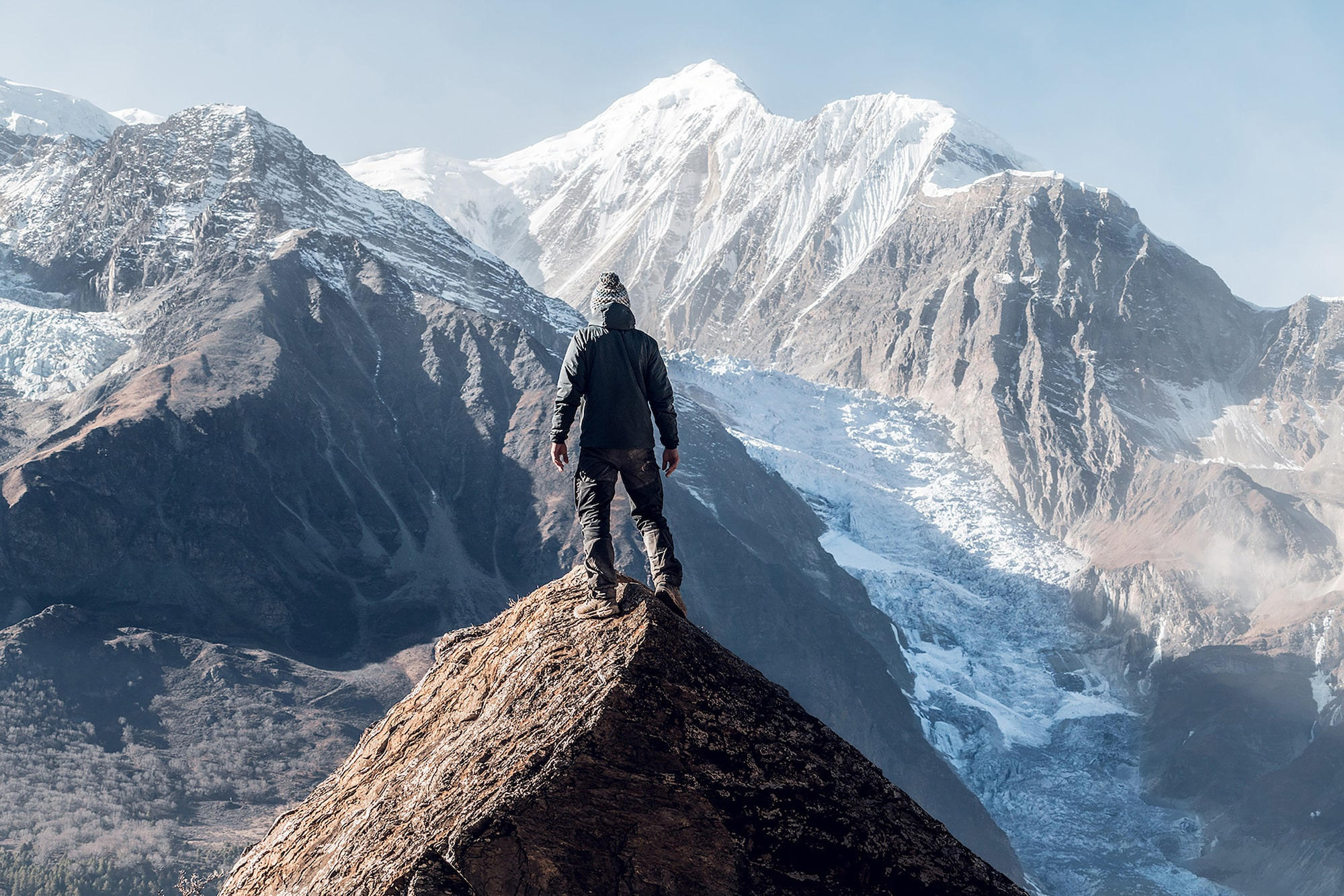 tolis fragoudis sony alpha 7RII man stands on the peak of a mountain gazing at distant snow covered mountains