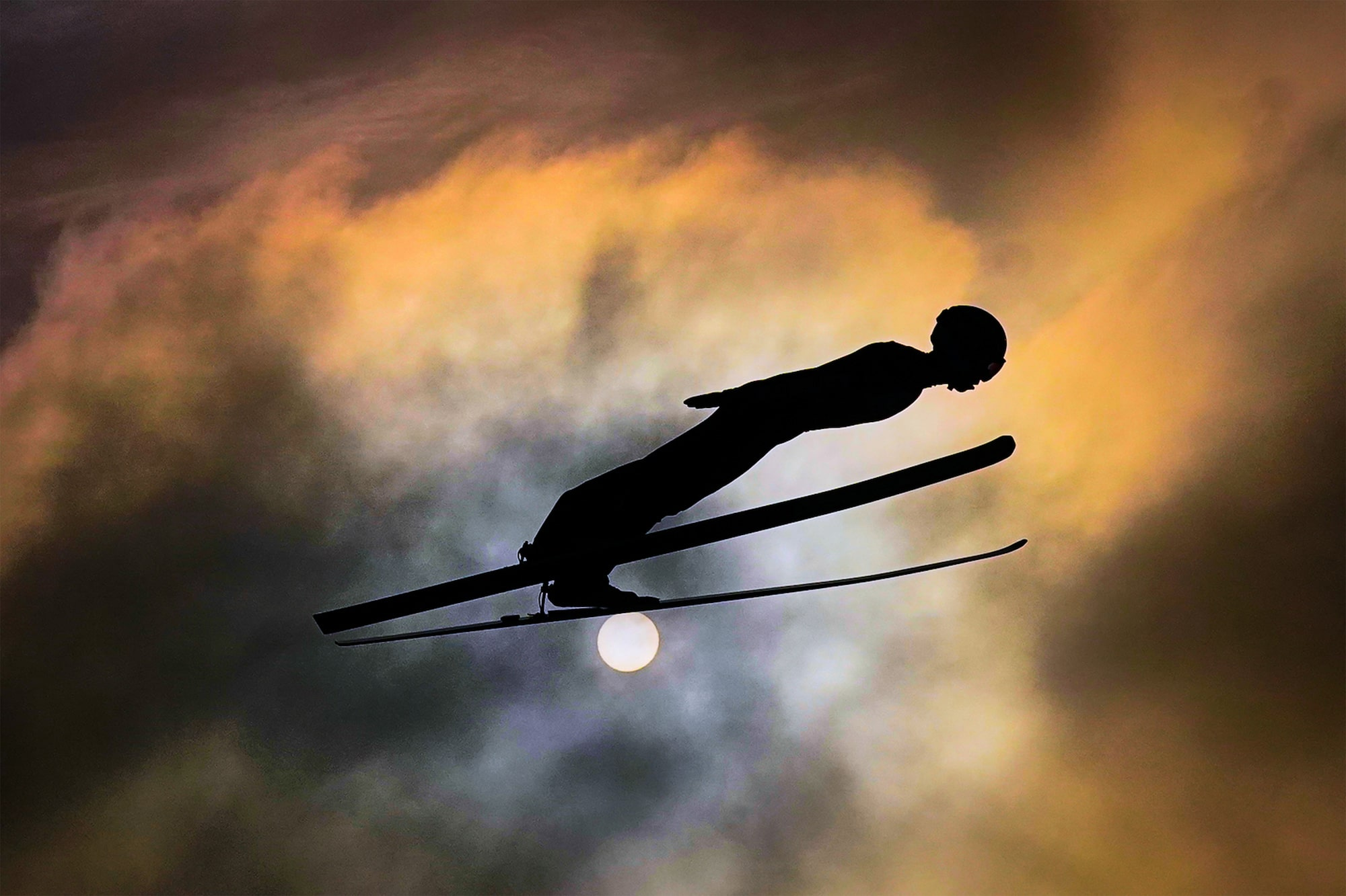 tomasz markowski sony alpha 9 ski jumper sideways on against an orange cloudy sun