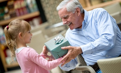 A girl is giving a present to her grand father.