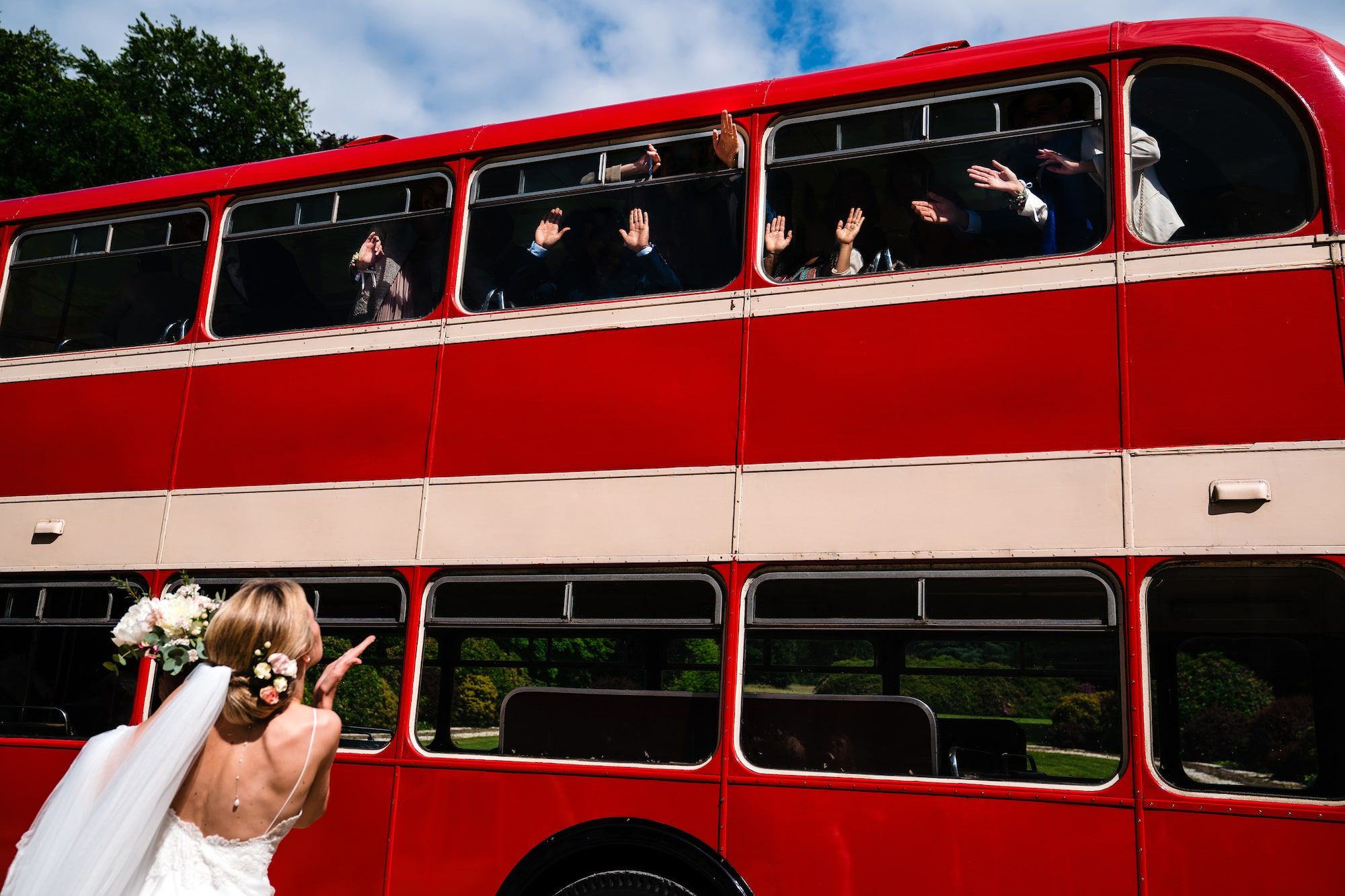 yves schepers sony alpha 9 a bride blowing her groomsmen a kiss as they sit on a red bus