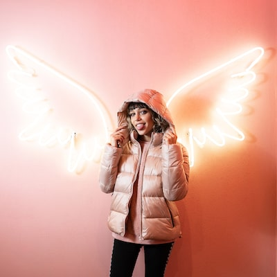 amedeo novelli sony alpha 9 girl standing in front of angel wings made from neon lighting