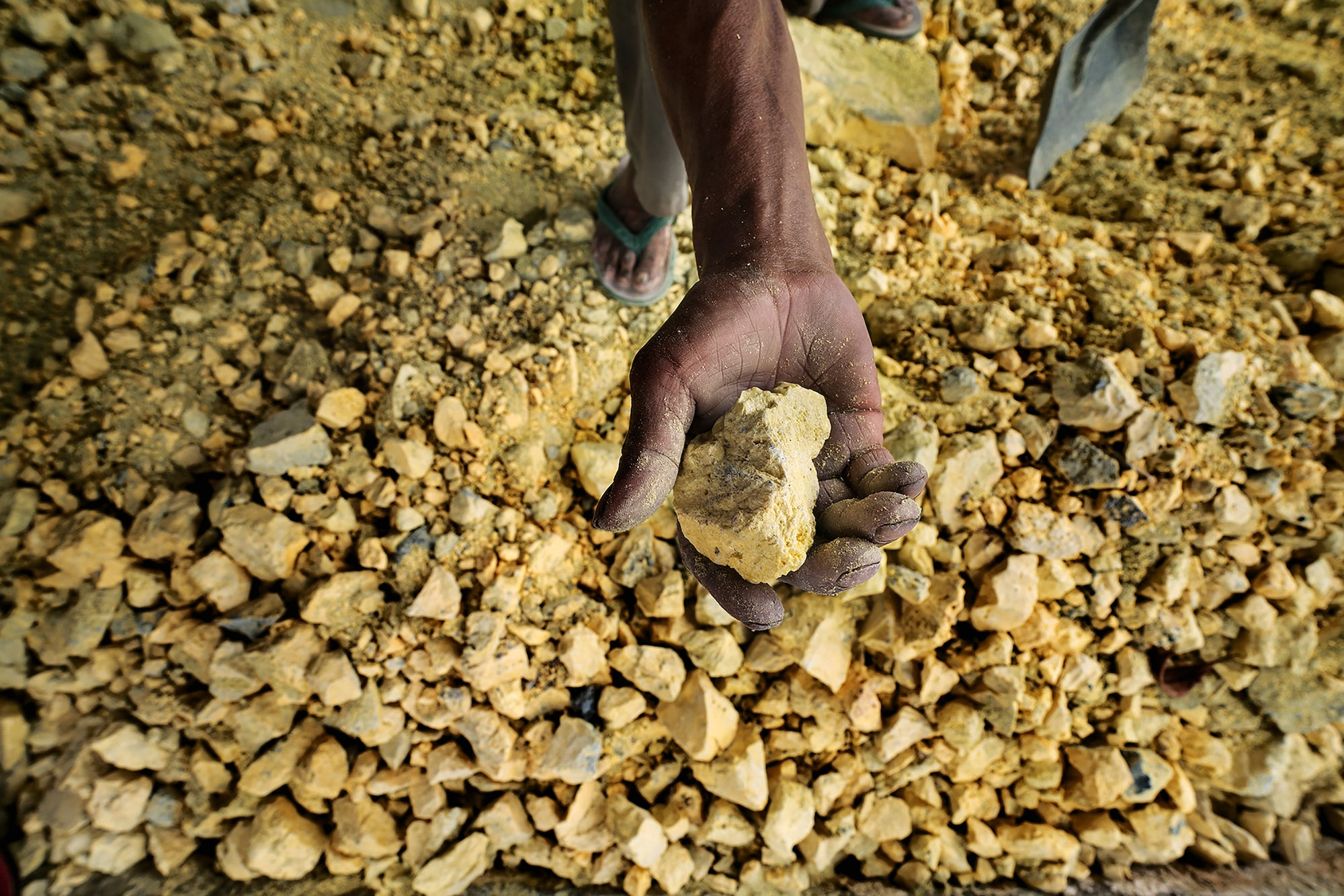andrea frazzetta sony alpha 7RII miner uns his hands through a pile of sulfur rocks