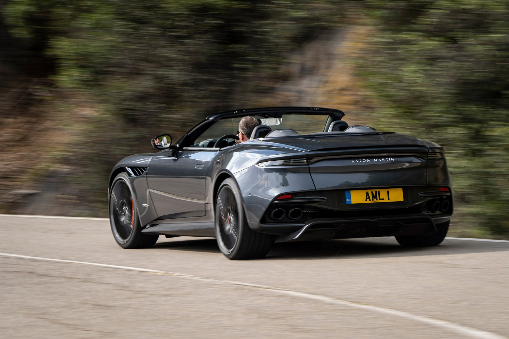dominic fraser sony alpha 6400 aston martin car shot from behind being driven along a mountain road