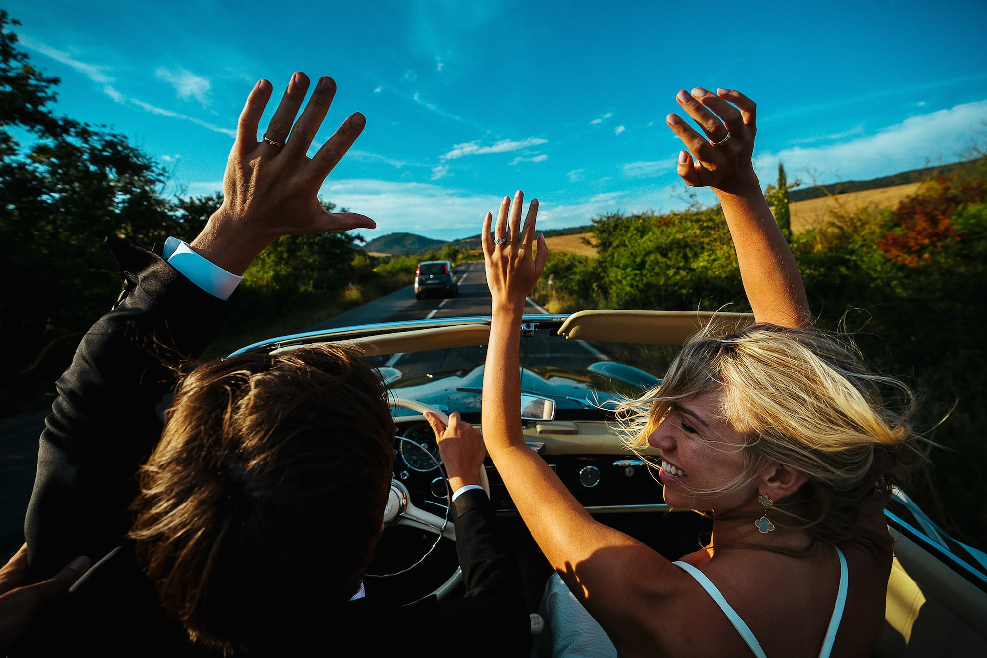 George Kasionis Stam Tsopanakis sony alpha 7m3 bride and groom raise hands in joy as they ride on a sunny tuscan road