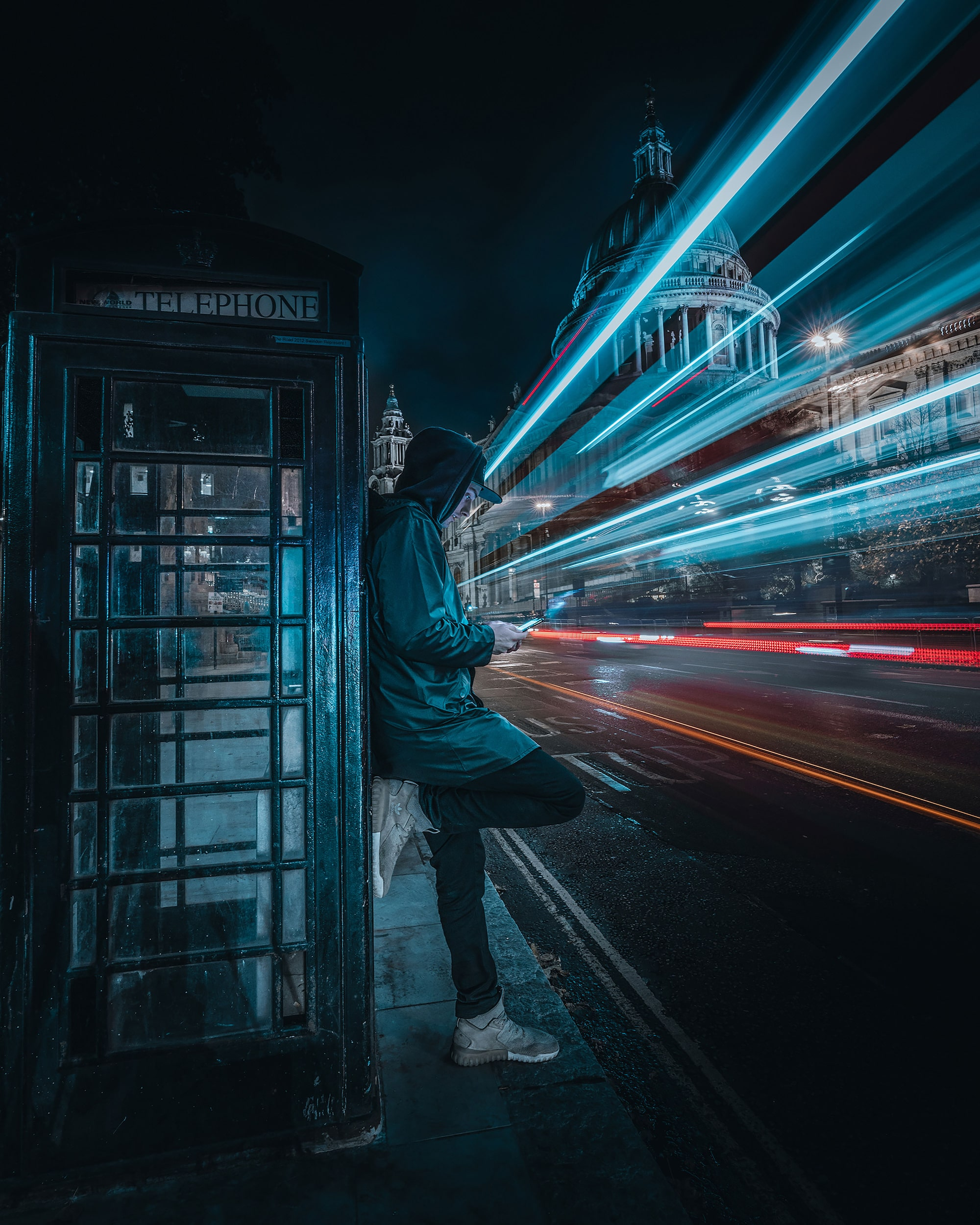 mike will sony alpha 7RIII man leans against a telephone box at night as traffic trails wind through the street