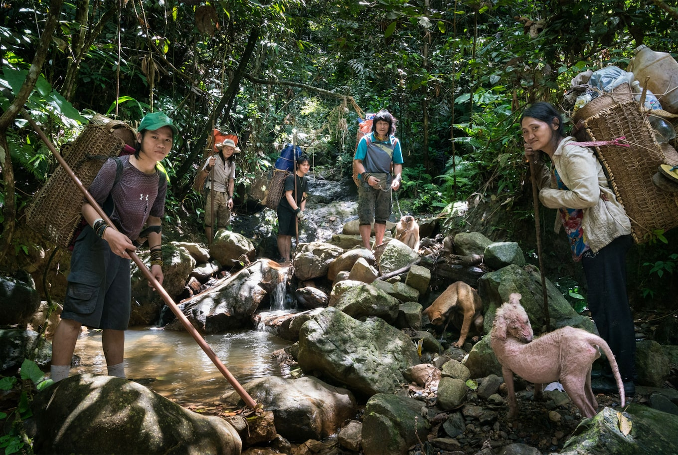 Tomas Wuethrich sony alpha 9 group of tribeswomen stand by a jungle pond with wicker baskets on their backs