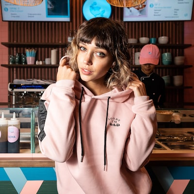 amedeo novell sony alpha 9 girl stands in front of a deli counter wearing a pink hoodie