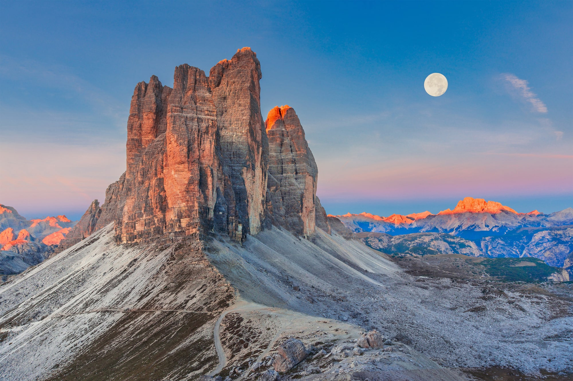 dmytro korol sony nex 6 a striking mountain peak at dusk illuminated with a warm glow with a full moon visible behind