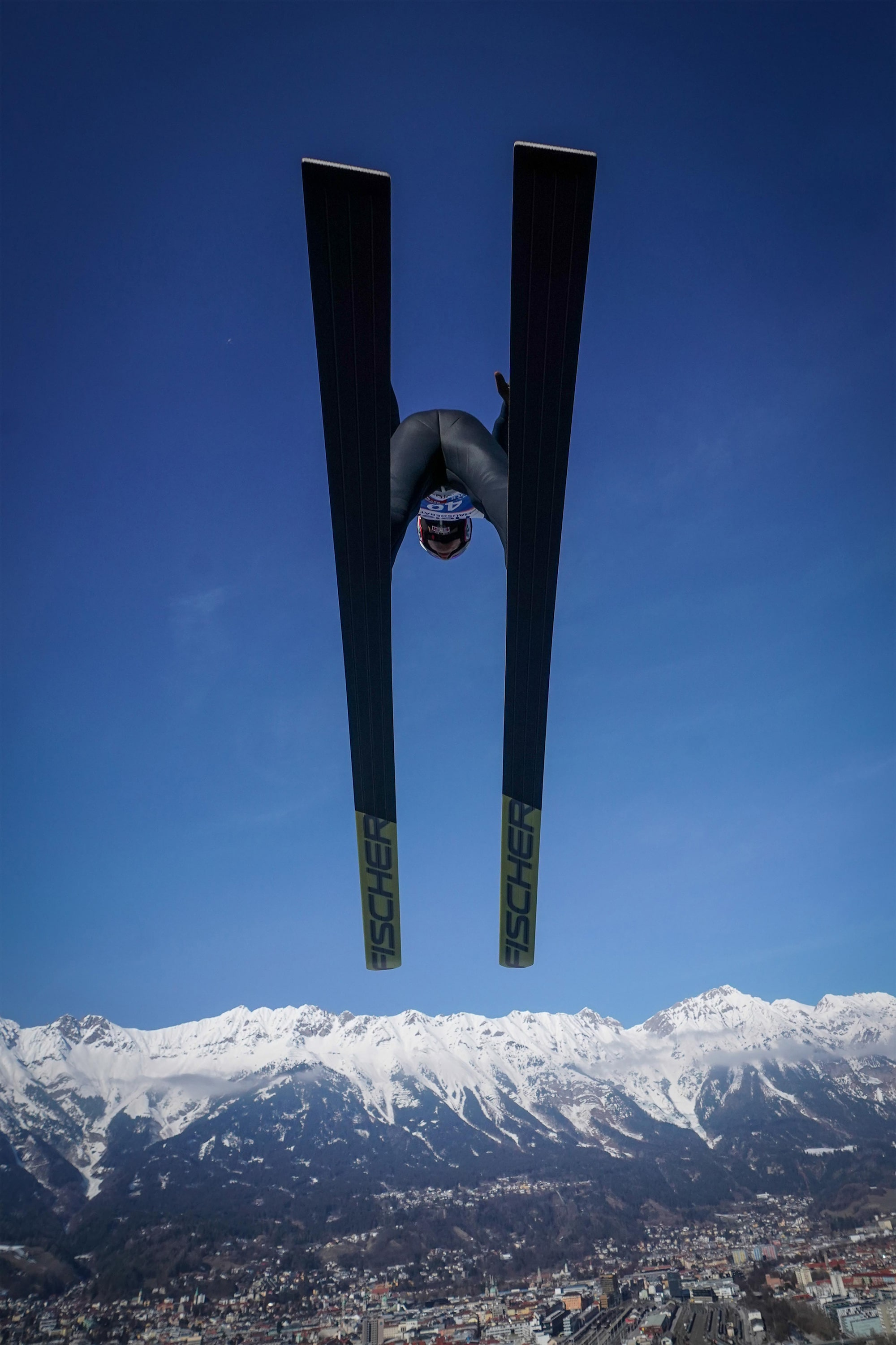 tomasz markowski sony alpha 9 looking up at a ski jumper as he passes overhead against a deep blue sky