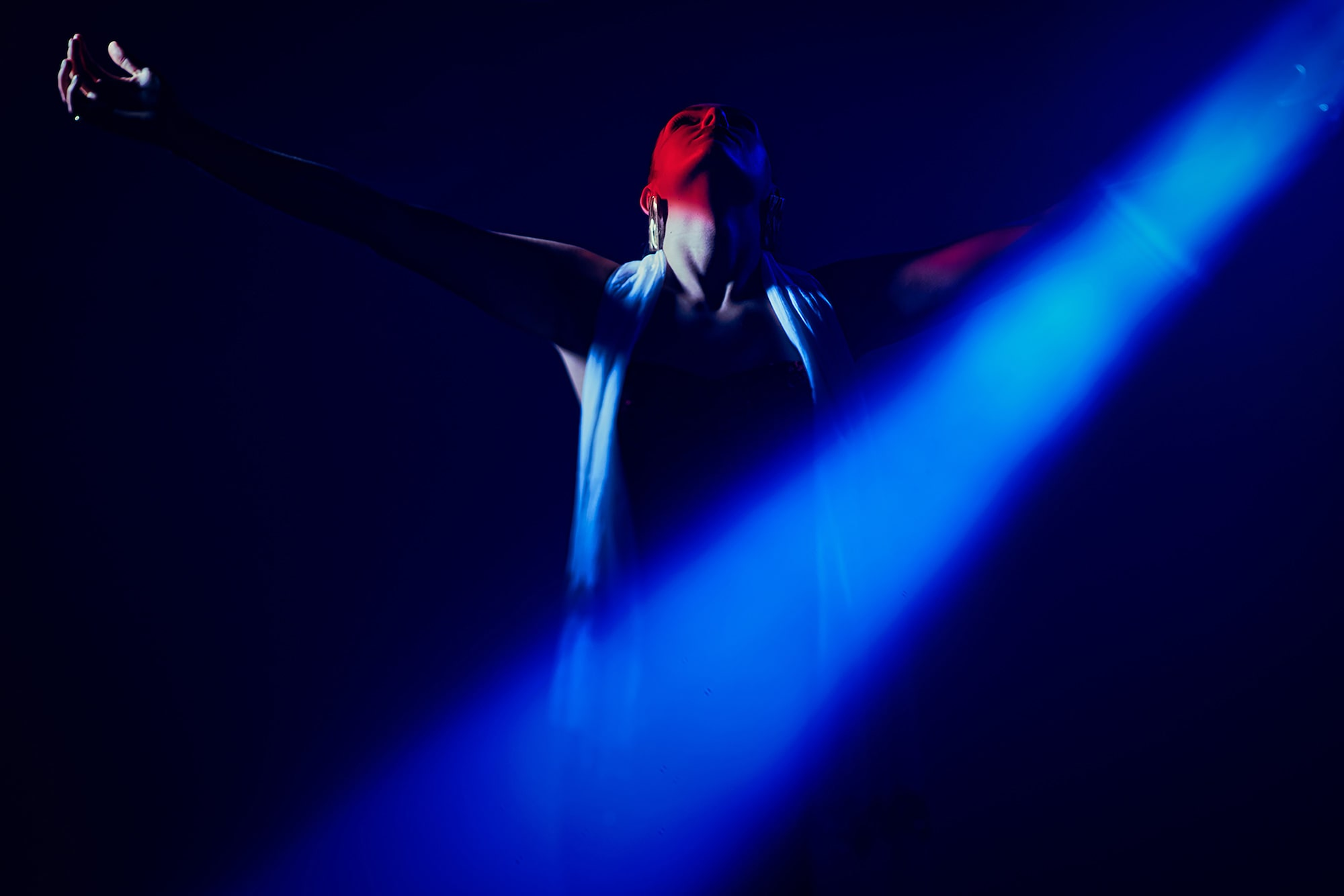 frank doorhof sony alpha 7RIII lady stands with her arms outstretched in the dark with a blue light shining across her