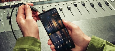 Person plugging in 3.5mm audio jack to Xperia 1 III in front of a mixing desk